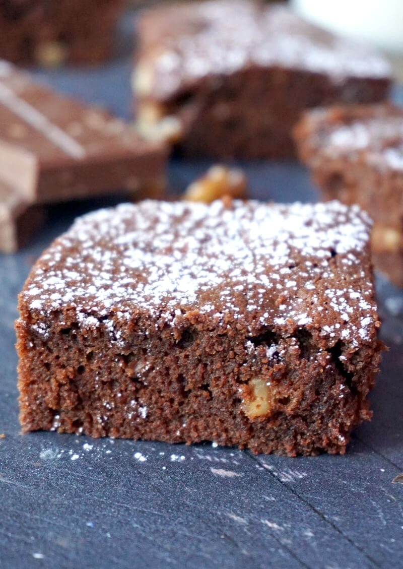 A square walnut brownie with other squares in the background