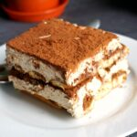 A white plate with a slice of dalgona tiramisu
